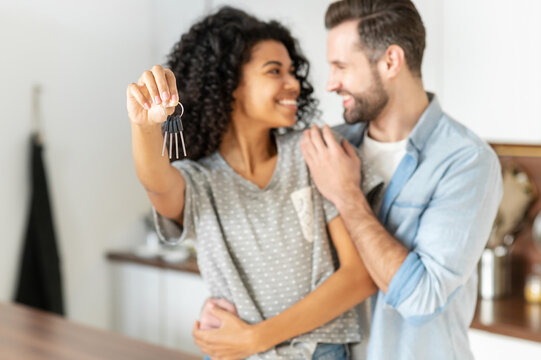 Happy young interracial married couple holding a key ring in hand, hugging and looking at each other with love, standing in the modern kitchen of their new home, excited owners of a family apartment