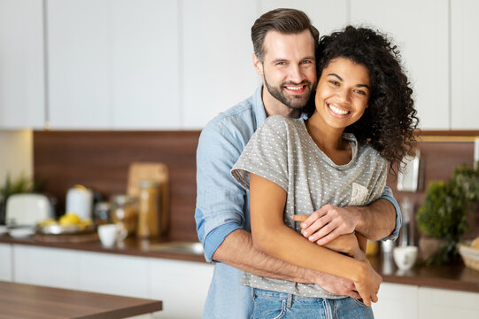 Smiling man hugging from behind charming African American woman, two people standing and joyfully looking at camera. Young international couple happily spending time in cozy modern kitchen at home.