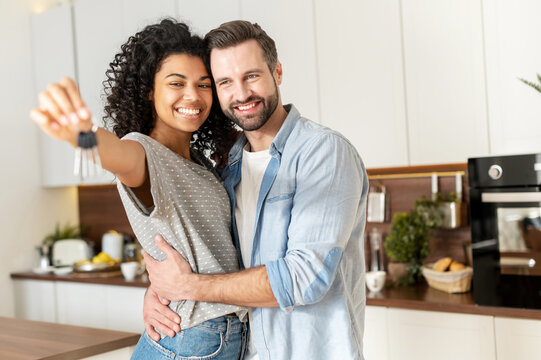 Young interracial married couple homeowners smiling, showing keys from a new apartment, hugging and looking at the camera, standing in the kitchen and celebrating moving in a new home, family concept