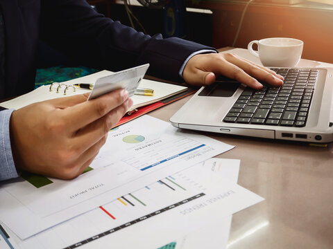 Midsection Of Businessman Holding Credit Card While Using Laptop In Office
