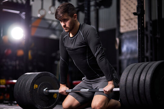 athletic man having workout and bodybuilding with barbells weight in dark gym and fitness club. young caucasian guy in sportswear training alone. sport, cross fit and bodybuilding concept