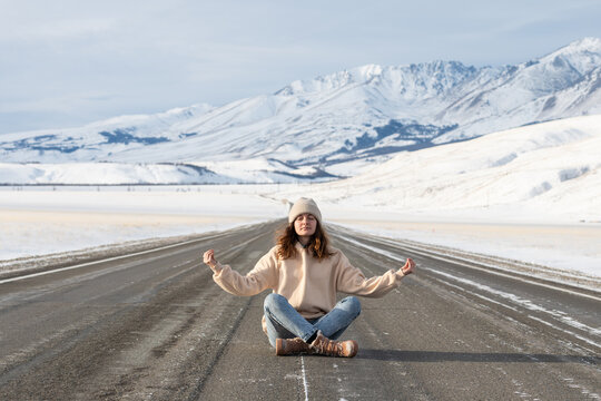Young woman meditating on the road
