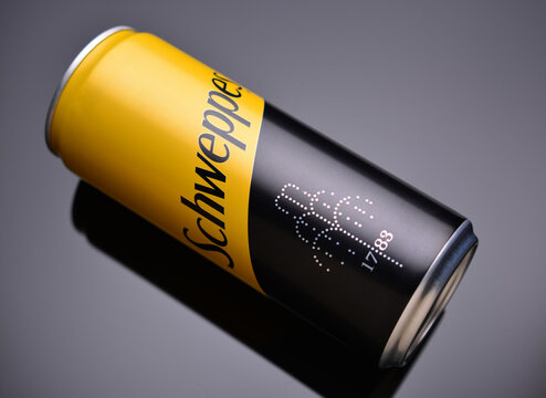 Schweppes drink in a tin can on a gray background