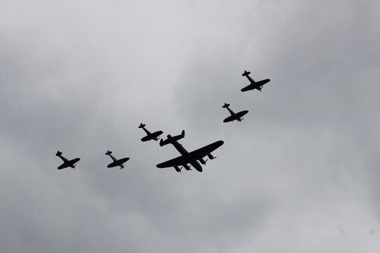 Low Angle View Of Silhouette Military Airplanes Flying Against Cloudy Sky