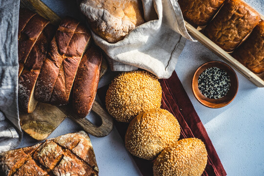 Overhead view of a variety of bread rolls and loaves of bread with sesame seeds