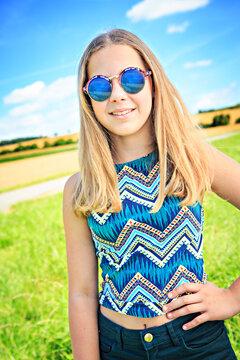 Portrait Of Smiling Teenage Girl Wearing Sunglasses Standing On Field