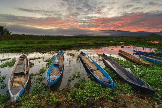 Row of Fishing boats moored on Lebo lake at sunset, Sumbawa, Indonesia