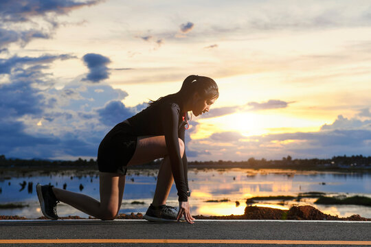 Woman getting ready to run along a lakeside road, Thailand