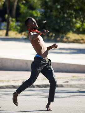 A man throws a rock as police clash with demonstrators during protests against Haiti's President Jovenel Moise, in Port-au-Prince
