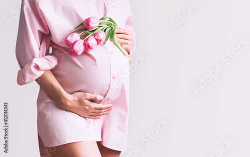 Pregnancy, Motherhood, Mother's Day Holiday concept. Young woman in maternity shirt dress with tulips flowers holds hands on belly. Beautiful pregnant woman waiting for baby birth.
