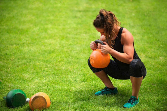 Mid Adult Woman Lifting Kettlebell While Crouching On Grassy Field