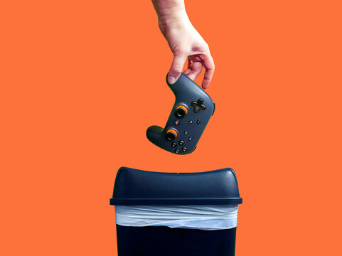 Seattle, WA / USA - circa November 2019: Closeup of a Google Stadia gaming controller being thrown into the trash can in frustration, against a colorful background