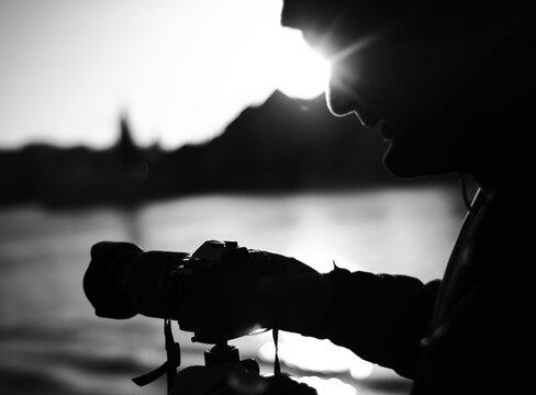 Close-up Of Silhouette Male Photographer Photographing With Camera Against Lake During Sunset