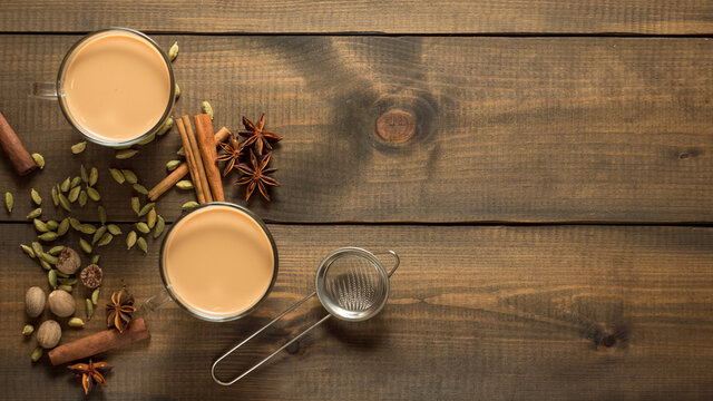 Two mugs with masala tea stand on a wooden table with spices. Top view. Copy space.