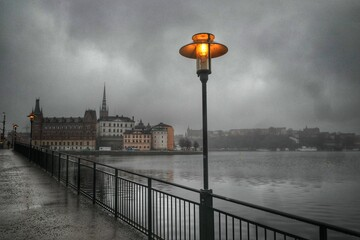 Street Light By River Against Buildings In City