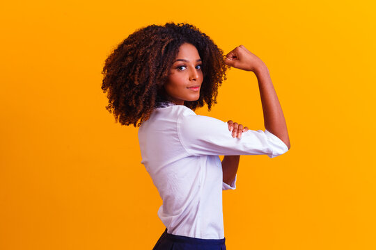 We can do it. Woman's fist of female power. Woman victim of racism. Abuse at work. The feminine power. Female empowerment. The strength of women. Yellow background.
