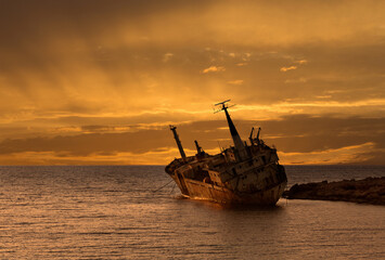 Abandoned Ship On Sea Against Sky During Sunset