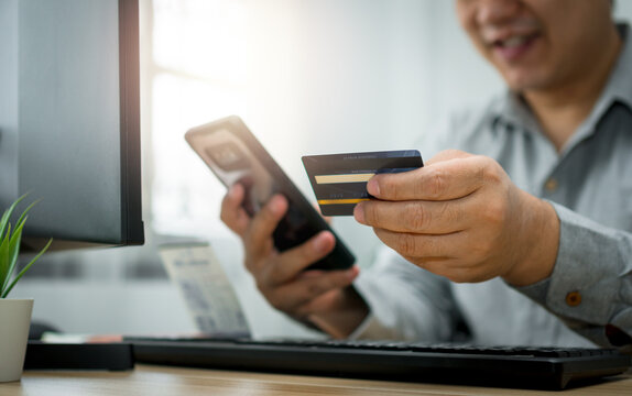 A Man holding credit card and using smartphone for payment online for purchase after order products via the internet. The concept of technology for e-commerce (electronic commerce)