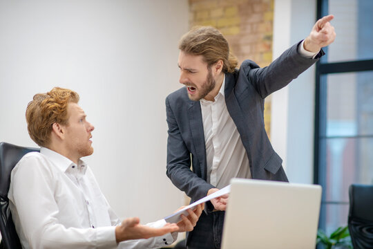 Screaming man pointing with hand and bewildered colleague