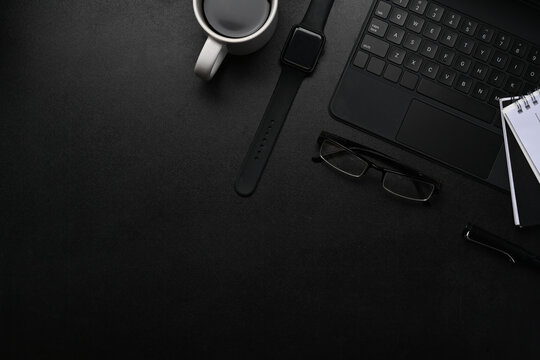 Above view of dark modern workspace with smart watch, notebook, wireless keyboard, glasses and copy space on black table.