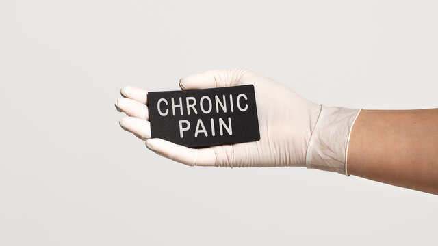 Closeup of the hand in a white sterile glove holding a card with text - CHRONIC PAIN