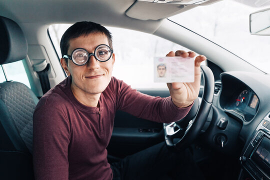 Funny nerd and geek in huge ridiculous glasses shows his driver's license. Concept of vision correction and fools on the road