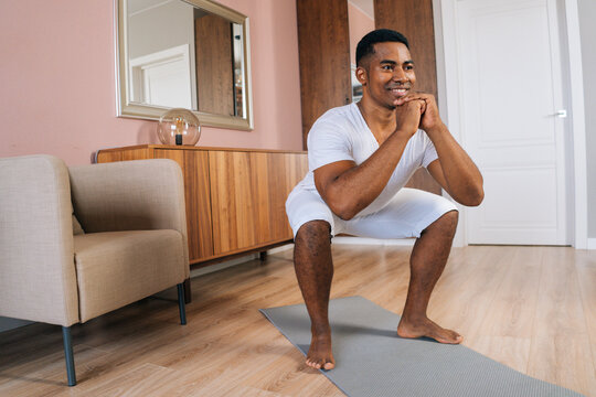 Front view of cheerful muscular African-American man wearing white T-shirt exercising and doing squats online in front of laptop at bright domestic room. Concept of sport training at home gym.