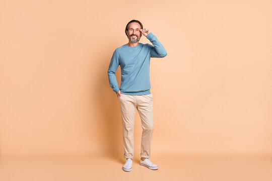 Photo portrait full body view of man touching glasses isolated on pastel beige colored background
