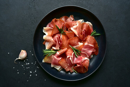 Slices of prosciutto di parma or jamon serrano (iberico)  on a black plate. Top view with copy space.