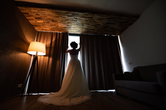 The bride in a wedding dress with her back turned, looking out the window. The interior is dark next to the lit lamp and she is wearing a white long wedding dress.