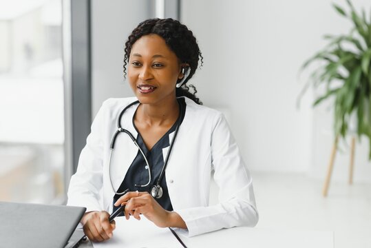 medicine, online service and healthcare concept - happy smiling african american female doctor or nurse with headset and laptop having conference or video call at hospital
