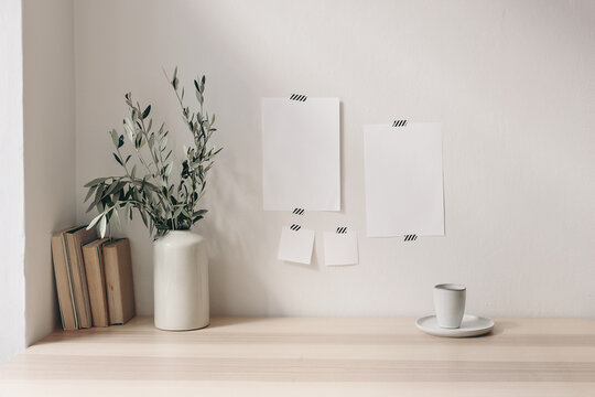 Breakfast still life. Cup of coffee, books on wooden desk, table. Empty notepads and posters mockups taped on white wall.Vase with olive branches. Elegant Scandinavian working space, home office.