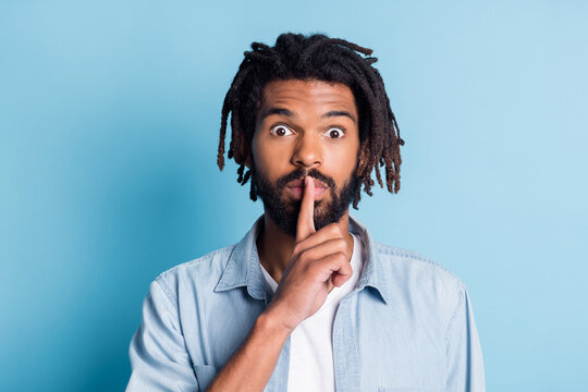 Portrait of nice suspicious guy showing shh sign dont speak isolated over vibrant blue color background