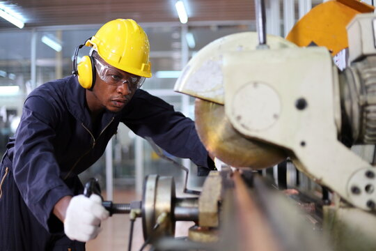 African American mechanic engineer worker wearing safety equipment is cutting copper tube using sawing machine in the factory