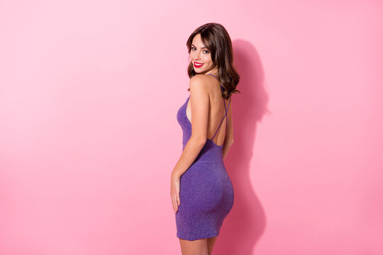 Photo of shiny pretty young lady wear purple glamour outfit standing showing sexy back isolated pink color background