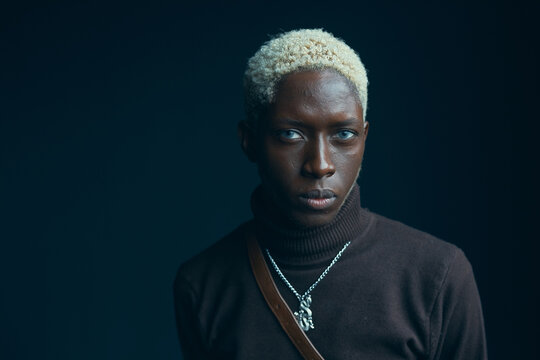 portrait of a dark-skinned handsome guy with white hair and blue eyes, who looks into the camera with a serious expression, he is dressed in a brown sweater over which hangs a silver chain