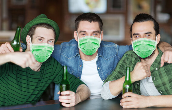 friendship, health and st patrick's day concept - male friends wearing face protective medical mask for protection from virus disease drinking bottled beer and hugging at bar or pub