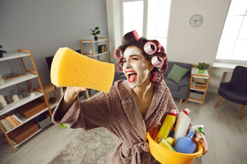 Fototapeta Tired desperate housewife holding yellow sponge and screaming like crazy while cleaning house. Funny young woman in hair rollers and beauty skin care face mask tidying up home, singing and having fun obraz