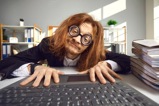 Man sitting at office desk and typing on keyboard. Funny nerd with long ginger hair searching for information on the Internet. Crazy looking computer geek in round thick lens glasses working on laptop
