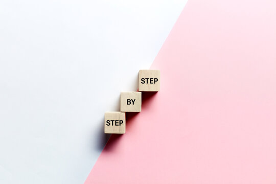The words step by step on wooden cubes against pink and white background. Progress or growth in career or business