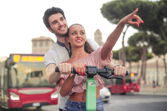 Couple riding e-scooter during vacation
