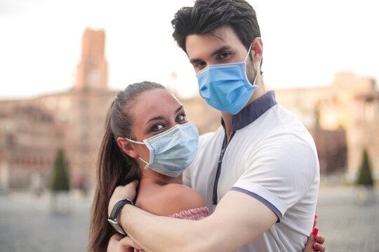 Couple with mask embracing outdoor