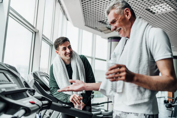 Portrait of two men in the gym, they communicate with each other on treadmills and drink water. Cardio, sports, health Wall mural