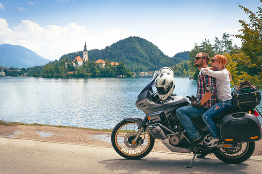 Couple in love travel together sit on touring motorcycle with bags. Tourism and vacation. Sunny summer day. Bled lake, island, castle and mountains in background, Slovenia, Europe
