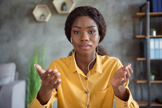 Photo of serious dark skin business woman talk web cam meeting wear headphones work in office indoors workplace