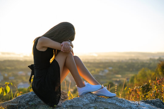 Young depressed woman in black short summer dress sitting on a mountain hill thinking outdoors at sunset. Lonely female contemplating in warm evening in nature.
