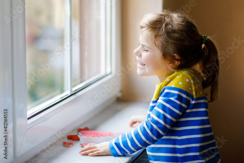 Cute little girl by window with lots of dough hearts as gift for Valentine's day, Mother's day or birthday. Adorable happy smiling child indoors.