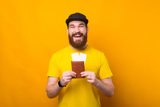 Portrait of amazed smiling man with beard holding passport and airplane tickets.