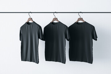 Make a sign concept with three blank black t-shirts hanging on a rail at white background. Mockup. 3D rendering
