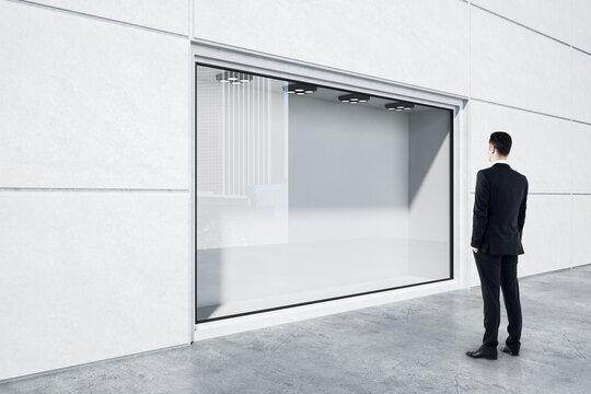 Businessman in black suit looking at empty street shop window in light building outside. Mockup